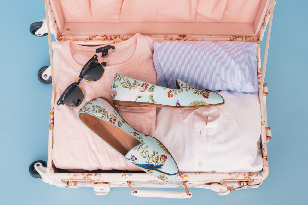 Suitcase with sunglasses and pastel clothes to pack for Hawaii