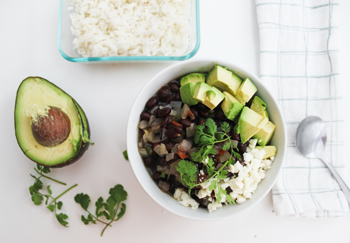 black bean soup in a bowl with avocado and cilantro in white background