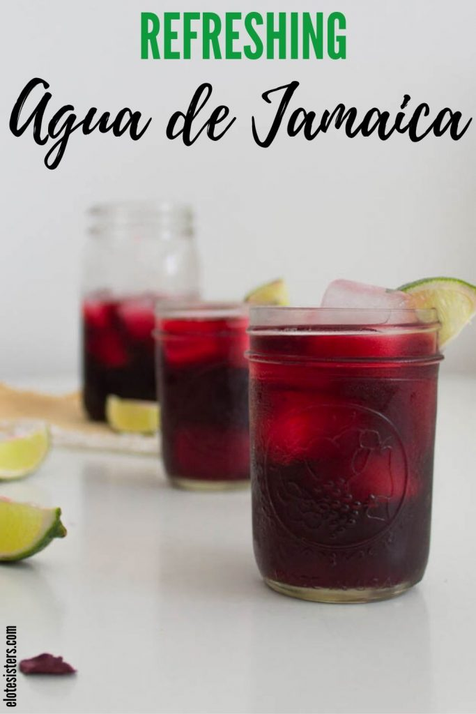 "3 mason jars with red purple hibiscus drink and lime wedges in foreground with text on top of image that reads ""refreshing Agua de Jamaica"""