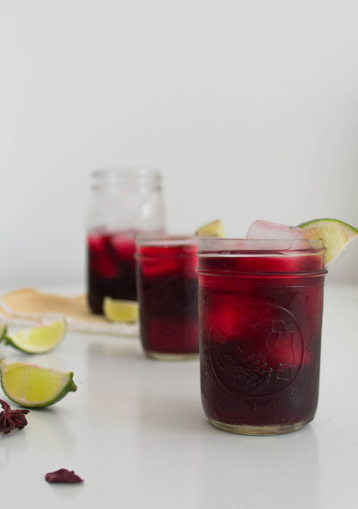 3 mason jars with red purple hibiscus drink and lime wedges in foreground