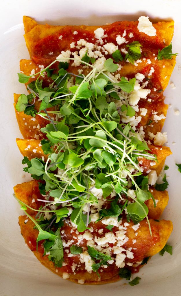 Up close of entomatadas recipe topped with micro greens, cheese and red sauce